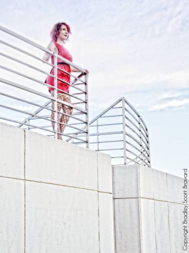 Woman in red dress standing on concrete ledge and looking into the distance