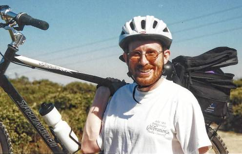Photograph of Bradley Bravard carrying bicycle, 1999
