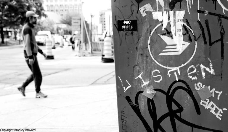 "Man walking on sidewalk with graffiti ""Listen"" on utility post"