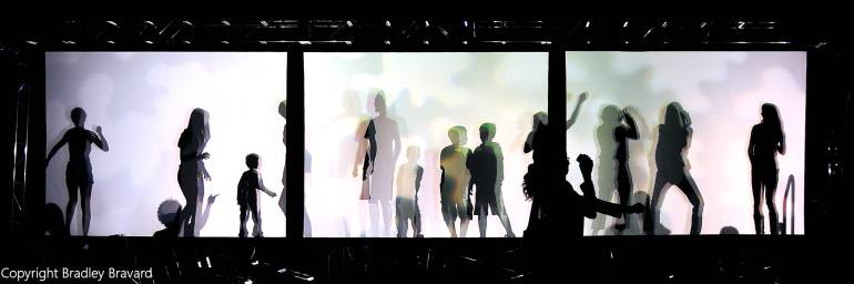 Silhouettes of people behind a white screen