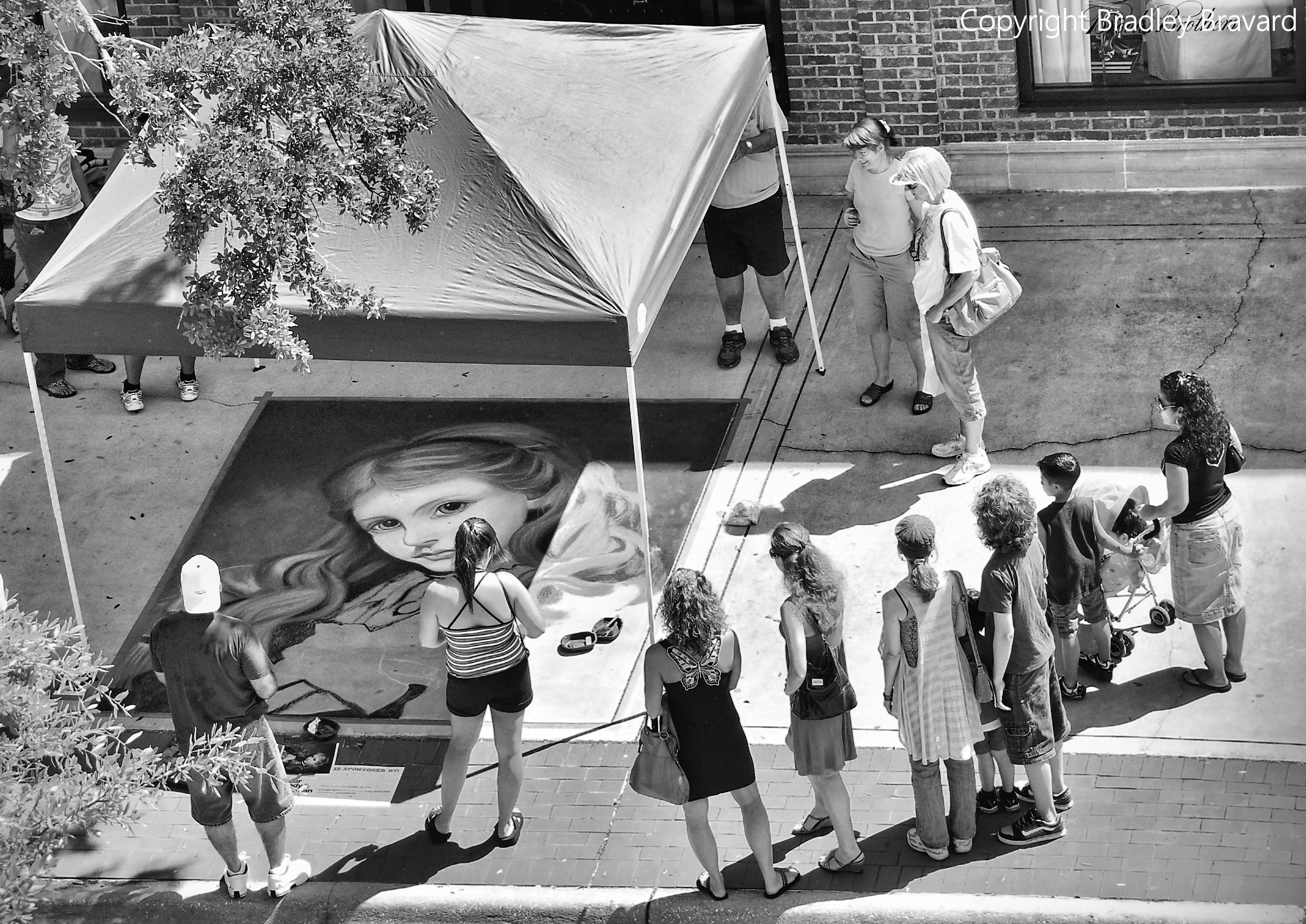Black and white photo of sidewalk chalk mural observed by group of people