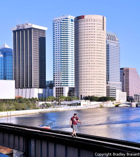 Photo of Tampa, Florida, skyline with person walking on bridge in foreground