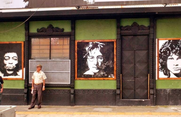 Two men standing on sidewalk and storefront with black and white portraits of Jimi Hendrix, John Lennon, and Jim Morrison