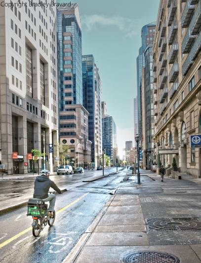 Photograph of bicyclist on city street surrounded by tall buildings in Montreal, Canada