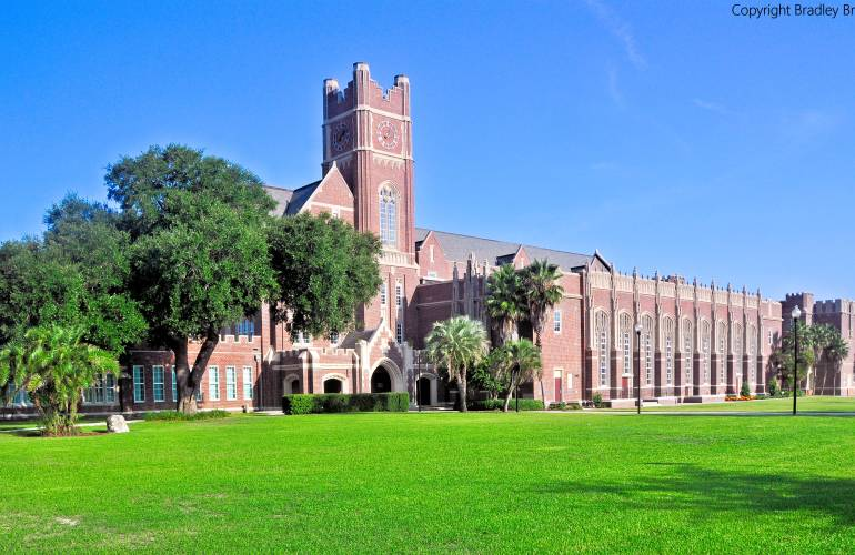 Hillsborough High School (large brick building) with blue sky and green grass in foreground, in Tampa, Florida