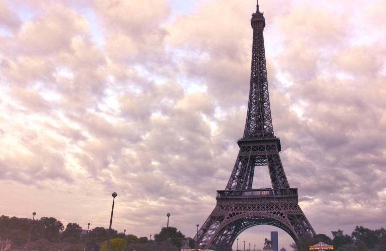 Eiffel Tower in Paris with scattered clouds in sky