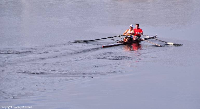 Photo of two men rowing a kayak on a river