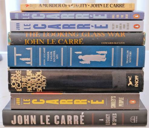 Copies of John le Carre's George Smiley novels stacked horizontally, with the exception of The Secret Pilgrim