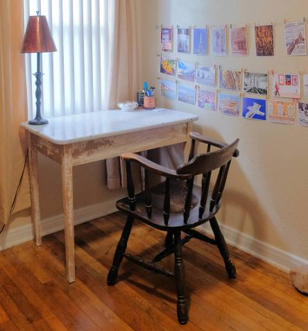 Home office with chair, desk, lamp, window, and photos displayed on wall