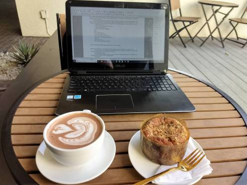 Photo of laptop computer on outdoor table at a coffee shop, with a muffin and a mug of hot chocolate