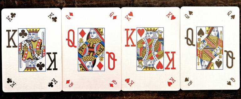 Photo of 4 playing cards: King of clubs, queen of diamonds, king of hearts, and queen of spades