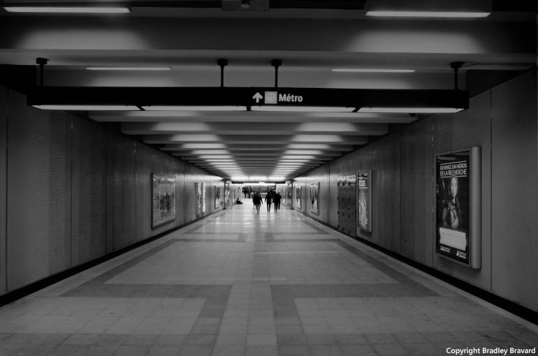 Black and white photo of a group of people at the far end of a Montreal Metro tunnel