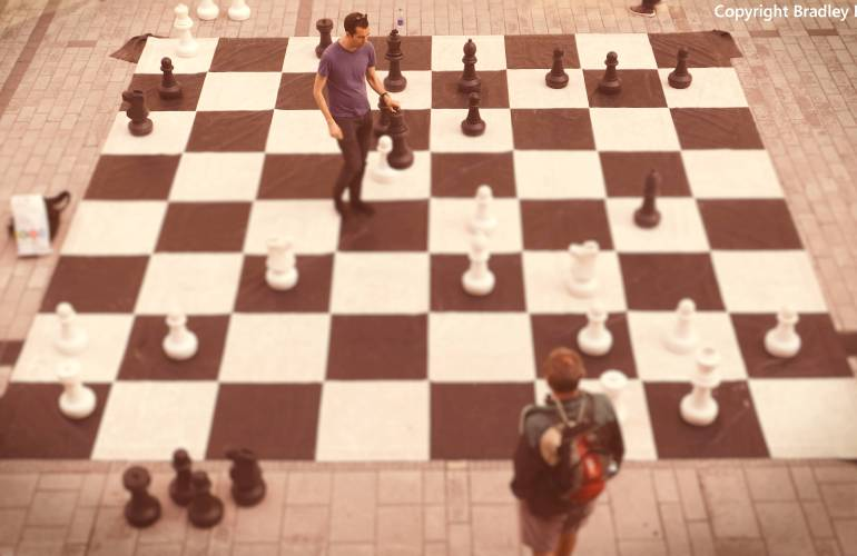 Photograph of 2 men playing chess on a very large chess board
