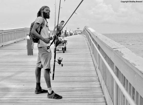 Black and white photo of man carrying fishing poles on pier at Atlantic Ocean coastline