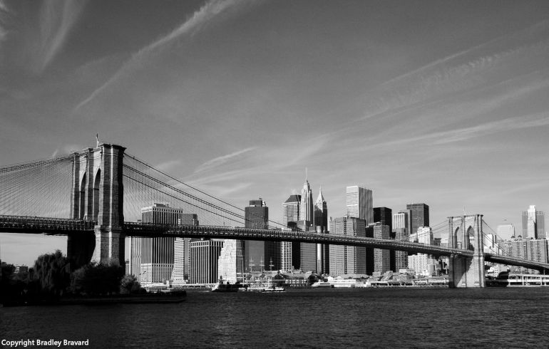Black and white photo of lower Manhattan skyline behind the Brooklyn Bridge viewed across the East River