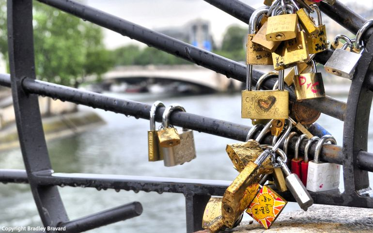 Padlocks attached to bridge over the Seine River in Paris