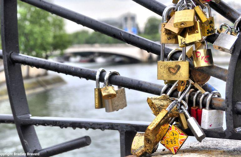 Padlocks attached to bridge over the Seine River in Paris