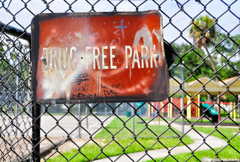 """Photo of """"Drug Free Park"""" sign on chain link fence surrounding a park"""