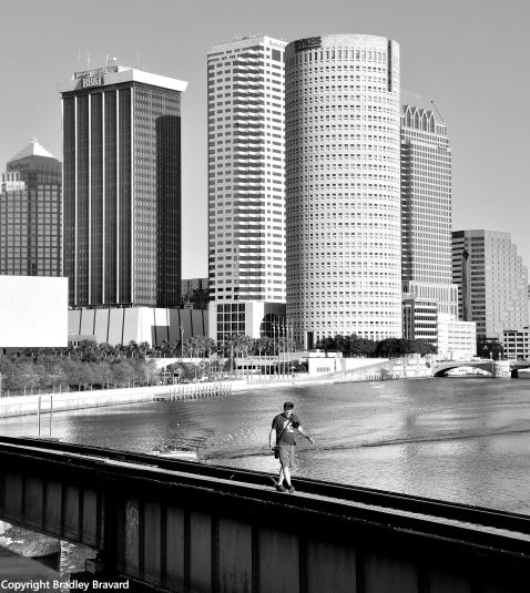 Black and white photo of downtown Tampa skyline, with a person crossing the Hillsborough River on a footbridge in the foreground