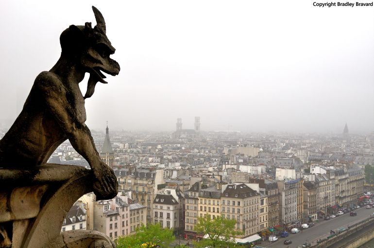 Color photo of Paris viewed from the roof of Notre Dame, showing a stone gargoyle in the foreground