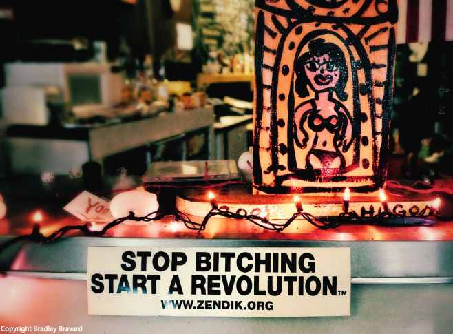 "Interior of coffee shop with sticker reading ""Stop bitching, start a revolution"" and hand-painted pinup art"