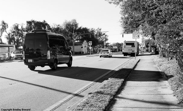 Black and white photo of street with van, car, and bus