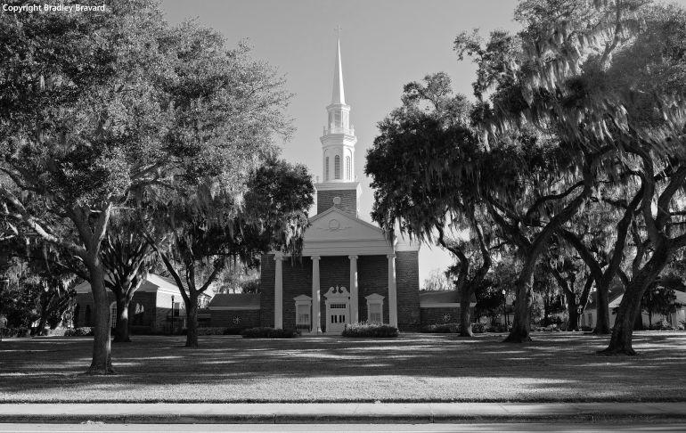 Black and white photo of church with tall steeple and trees with Spanish moss on both sides of church