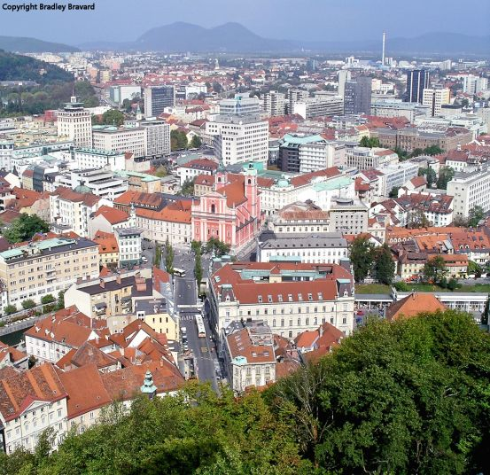Color photo of central Ljubljana, Slovenia, viewed from Ljubljana Castle, highlighting Preseren Square and the Franciscan Church of the Annunciation