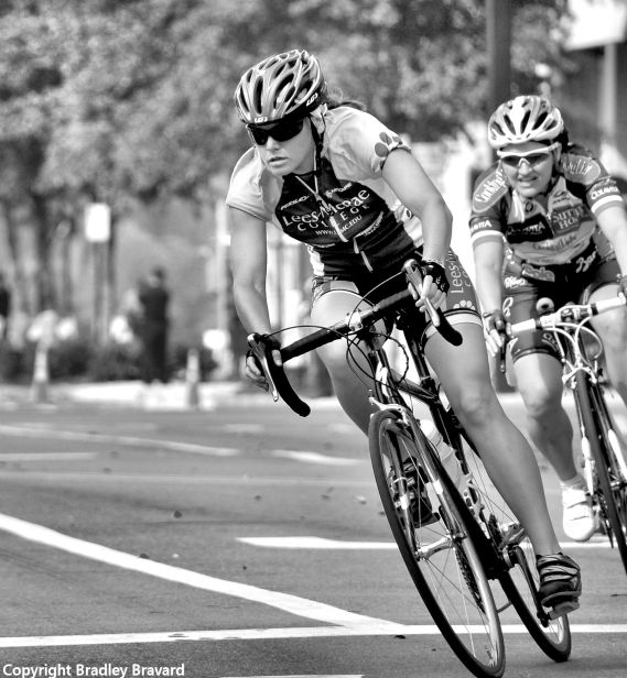 Black and white photo of two women on bicycles, wearing helmets and cycling gear