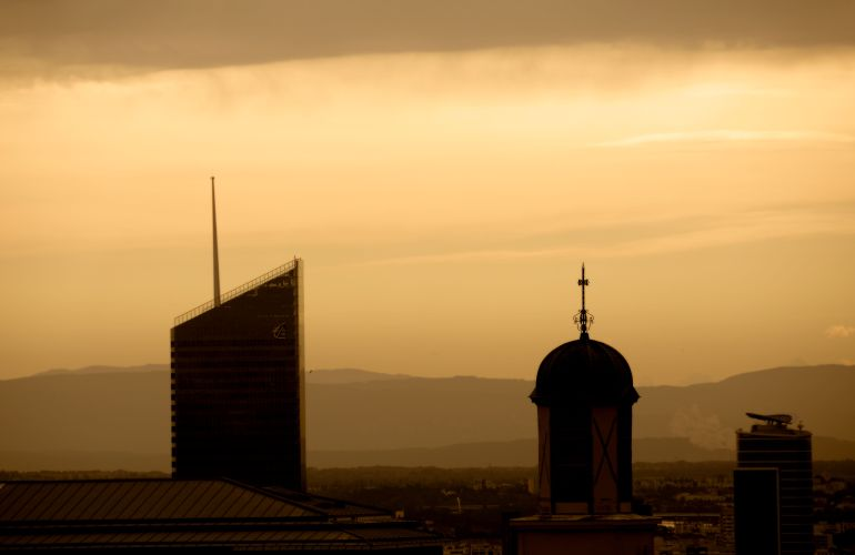 Two buildings in silhouette at sunrise