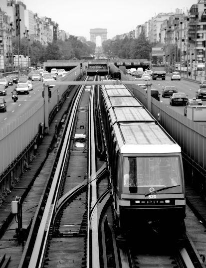 Black and white photo of Paris Metro train looking toward the Arc de Triomphe