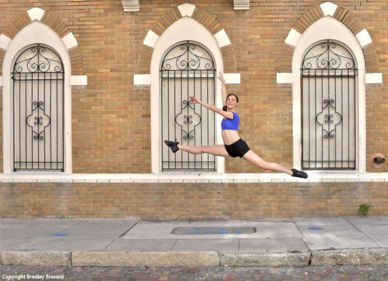 Ballet dancer jumping over sidewalk with brick building in background