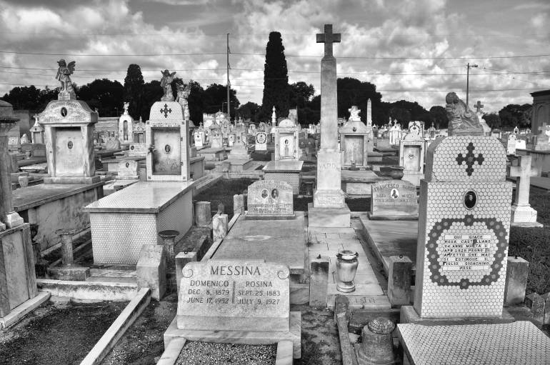 Black and white photo of historic cemetery with rows of above-ground tombs