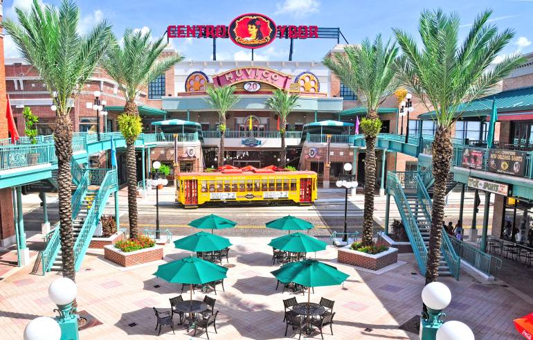 Photo of Centro Ybor shopping center with palm trees, pedestrian mall, and yellow trolley car