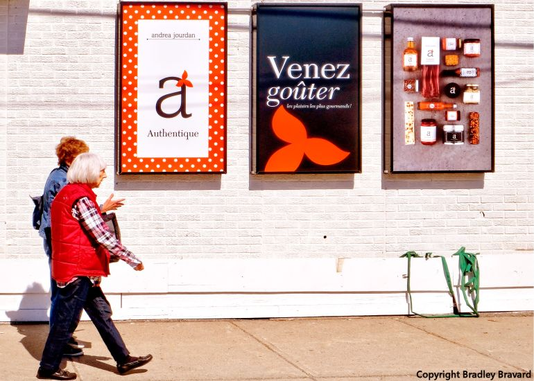 Photo of two women walking on sidewalk next to 3 posters on white brick wall