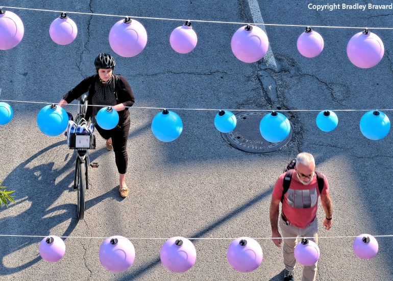 Photo of woman with bicycle and man walking in street viewed from overhead