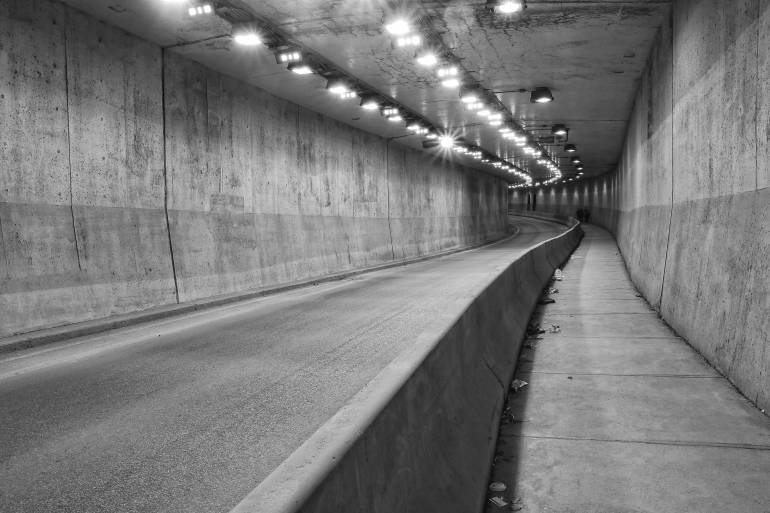 Black and white photo inside road tunnel with pedestrian sidewalk