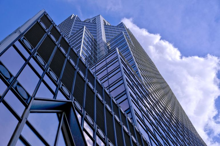 Photo at ground level looking up at glass skyscraper with partly cloudy sky in background