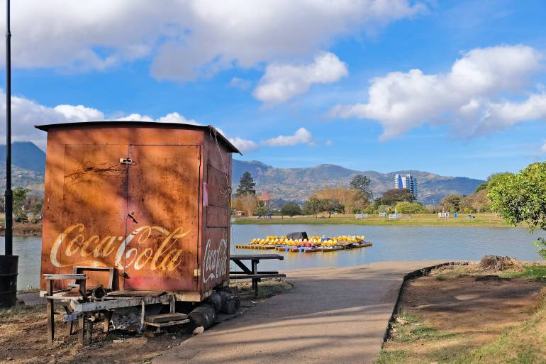 Wooden refreshment stand with Coca Cola logo in front of lake, with mountains and partly cloudy sky in background