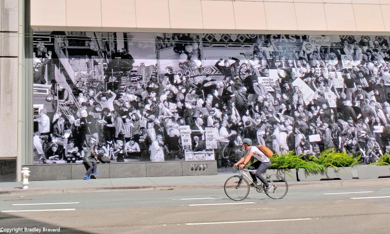 Man on bicycle in front of mural of crowd at San Francisco Museum of Modern Art