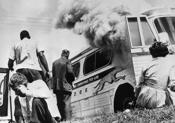 Photo of Freedom Riders outside burning bus in 1961
