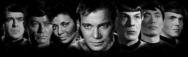 Black and white photo of original Star Trek cast members showing, left to right, James Doohan, DeForest Kelley, Nichelle Nichols, William Shatner, Leonard Nimoy, George Takei, and Walter Koenig