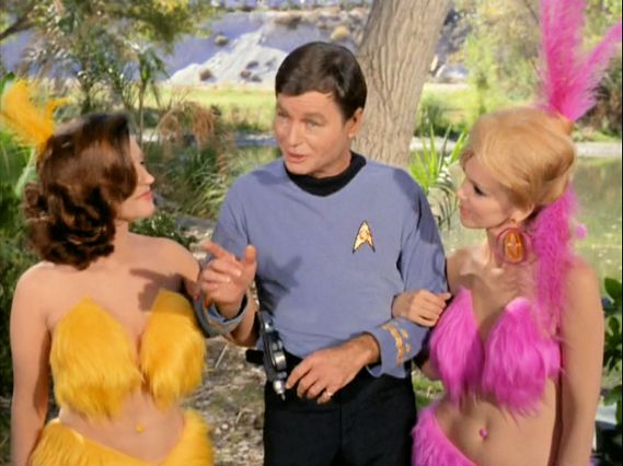 Image from Star Trek episode Shore Leave with McCoy in between two Vegas-style show girls
