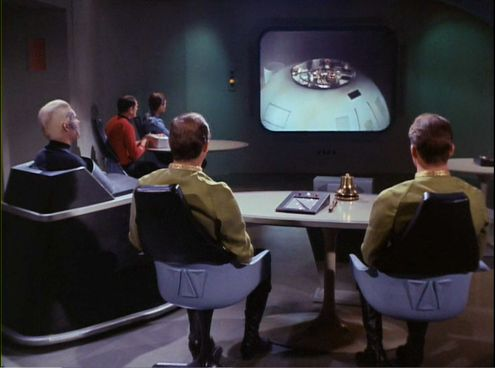 Episode from Star Trek episode The Menagerie, showing court martial with Pike, Mendez, and Kirk, and video of Enterprise bridge on display screen